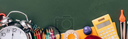 Photo for Top view of vintage alarm clock near school supplies on green chalkboard, panoramic crop - Royalty Free Image
