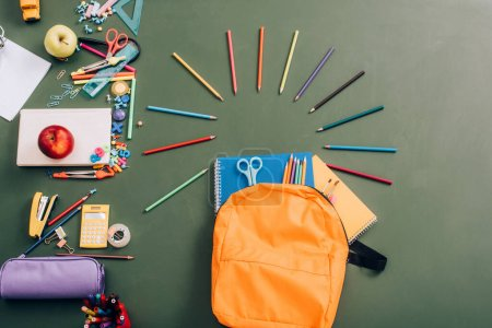 top view of backpack with notebooks, color pencils and scissors near school supplies on green chalkboard