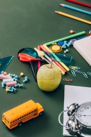 selective focus of ripe apple, school bus model and vintage alarm clock near school supplies on green chalkboard, high angle view