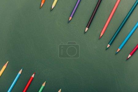 Photo pour Rangées de crayons de couleur sur tableau vert, vue du dessus - image libre de droit