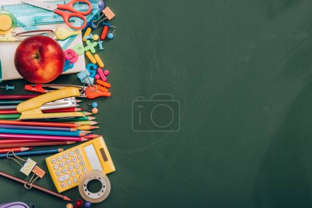 top view of ripe apple, calculator and school stationery on green chalkboard with copy space