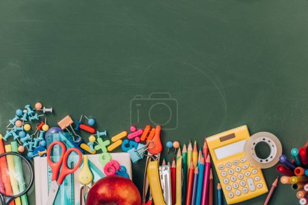 top view of apple, calculator and school supplies on green chalkboard