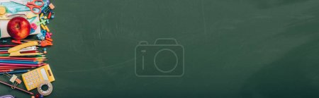 Photo for Top view of ripe apple and school stationery on green chalkboard, horizontal image - Royalty Free Image