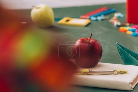 Photo pour Foyer sélectif de pomme et boussole diviseur sur livre près de fournitures scolaires sur tableau vert - image libre de droit