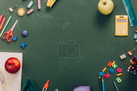 Photo for Top view of frame with ripe apples and school supplies on green chalkboard with copy space - Royalty Free Image