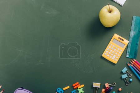 top view of ripe apple and calculator near school supplies on green chalkboard