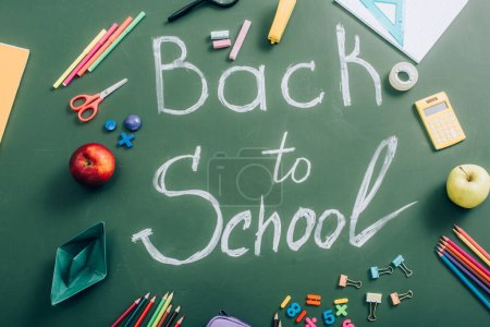 Photo for Top view of back to school inscription near school stationery and whole apples on green chalkboard - Royalty Free Image