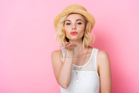 Photo for Young woman straw hat sending air kiss on pink - Royalty Free Image