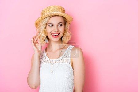 Photo pour Jeune femme en chapeau de paille touchant les cheveux et regardant loin sur rose - image libre de droit