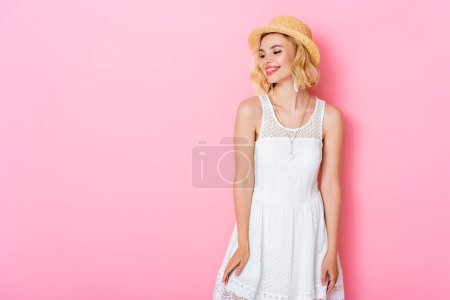 woman in straw hat and white dress standing on pink