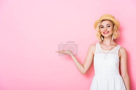 Photo pour Femme en chapeau de paille pointant avec la main sur rose - image libre de droit