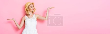 panoramic orientation of young woman in straw hat and dress pointing with hands on pink