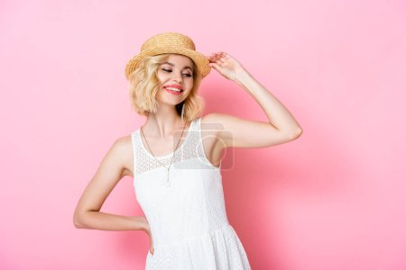 young woman touching straw hat and standing with hand on hip on pink