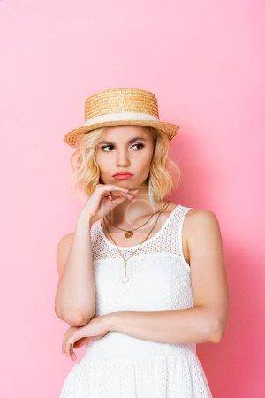 Photo pour Offensé femme dans chapeau de paille toucher le visage et détourner les yeux sur rose - image libre de droit