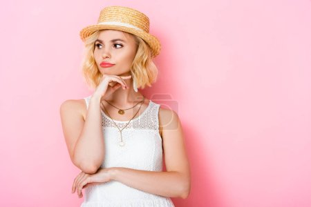 Photo for Pensive woman in straw hat touching face and looking away on pink - Royalty Free Image