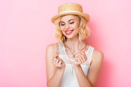 Photo pour Femme en chapeau de paille montrant geste d'argent avec les mains sur rose - image libre de droit