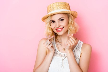 Photo for Woman in straw hat showing money gesture with hands on pink - Royalty Free Image