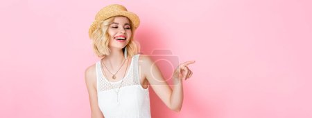 Photo for Horizontal image of woman in straw hat laughing and pointing with finger on pink - Royalty Free Image