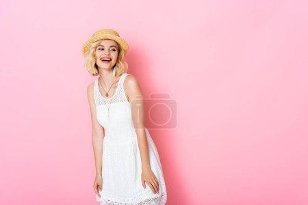 Photo pour Femme excitée en chapeau de paille riant et regardant loin sur rose - image libre de droit