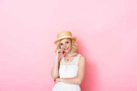 junge Frau mit Strohhut blickt in Kamera auf rosa