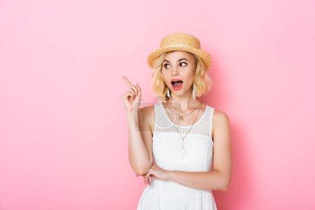 aufgeregte Frau mit Strohhut hat Idee für rosa