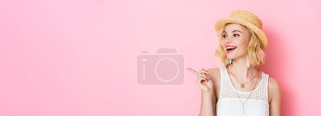 Photo for Horizontal image of woman in straw hat pointing with finger on pink - Royalty Free Image