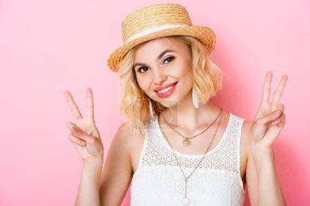 Photo pour Jeune femme en chapeau de paille montrant signe de paix sur rose - image libre de droit