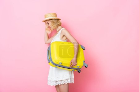 young woman in straw hat holding yellow luggage on pink