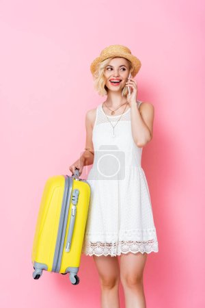 woman in straw hat holding luggage and talking on smartphone on pink