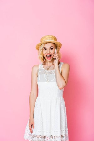 excited woman in straw hat talking on smartphone on pink