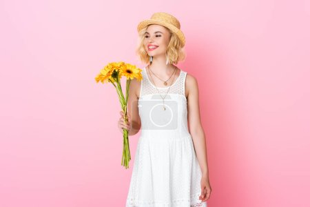 woman in straw hat and white dress holding yellow flowers on pink