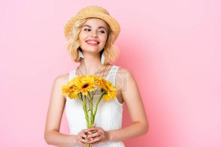 Photo pour Femme en chapeau de paille et robe blanche tenant des fleurs sur rose - image libre de droit