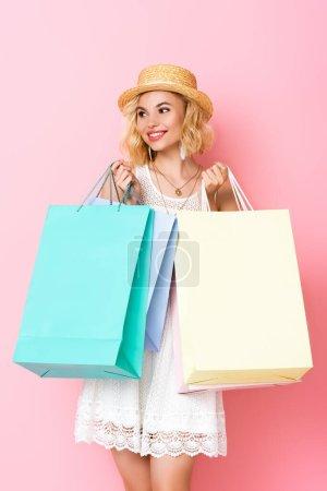 Photo pour Femme en chapeau de paille et robe tenant des sacs à provisions sur rose - image libre de droit