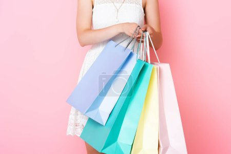 Photo for Cropped view of young woman holding shopping bags on pink - Royalty Free Image