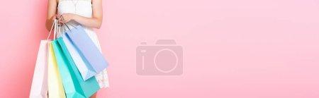 Photo pour Récolte panoramique de jeunes femmes tenant des sacs à provisions sur rose - image libre de droit