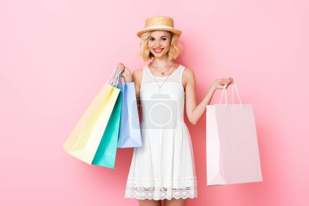 young woman in white dress holding shopping bags on pink