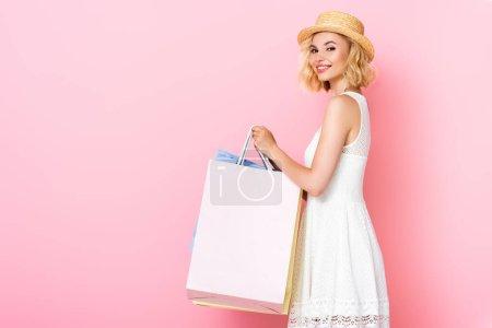 Photo pour Femme en robe blanche et chapeau de paille tenant des sacs à provisions sur rose - image libre de droit