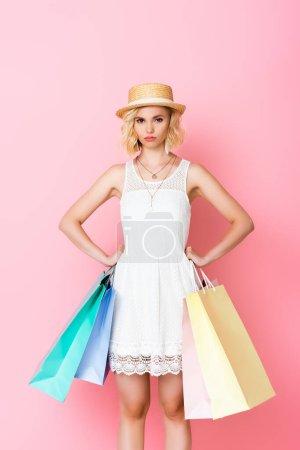 Photo pour Offensé femme en robe blanche et chapeau de paille tenant des sacs à provisions tout en se tenant debout avec les mains sur les hanches sur rose - image libre de droit