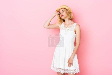 Photo pour Jeune femme fatiguée en chapeau de paille et robe blanche touchant le visage sur rose - image libre de droit