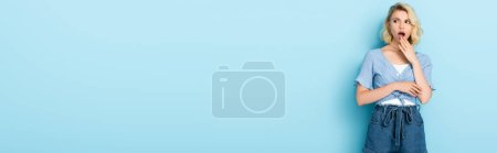 Photo for Panoramic shot of shocked young woman in shorts standing and covering mouth on blue - Royalty Free Image