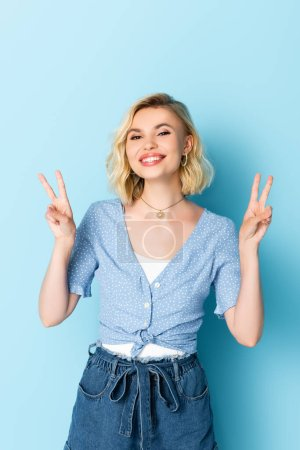 woman looking at camera while showing peace sign on blue