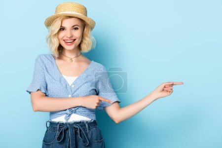 Photo for Woman in straw hat pointing with fingers and looking at camera on blue - Royalty Free Image