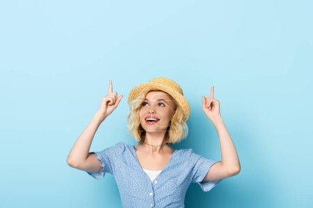 junge Frau mit Strohhut zeigt mit den Fingern und blickt auf blau