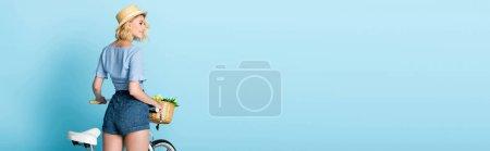 Photo pour Concept panoramique de femme en short debout près de vélo sur bleu - image libre de droit