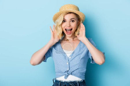 excited young woman in straw hat gesturing and looking at camera on blue