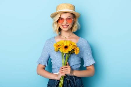 Photo for Woman in straw hat and sunglasses holding flowers on blue - Royalty Free Image