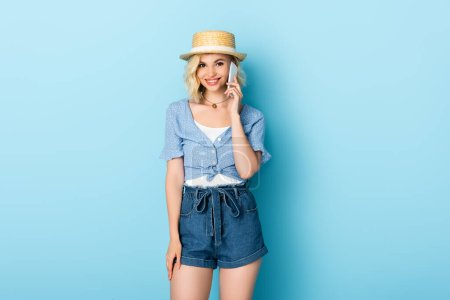 Photo for Young woman in straw hat talking on smartphone while standing on blue - Royalty Free Image