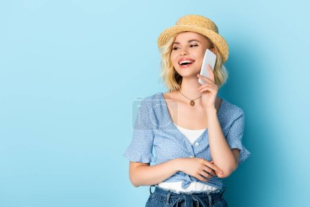woman in straw hat with open mouth talking on smartphone on blue