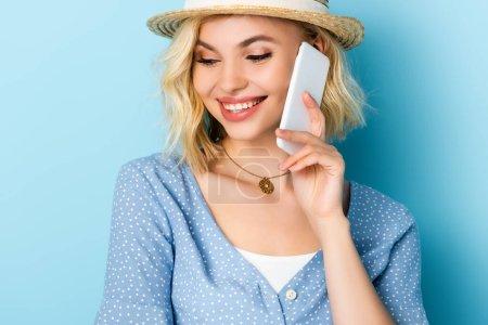 junge Frau mit Strohhut redet auf Smartphone auf blau