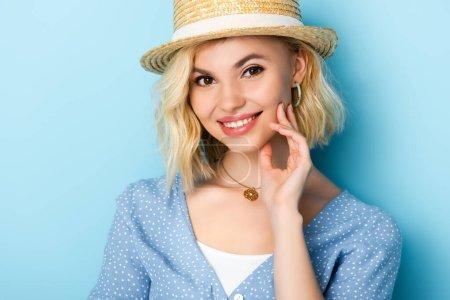 Photo pour Jeune femme en chapeau de paille regardant la caméra sur bleu - image libre de droit